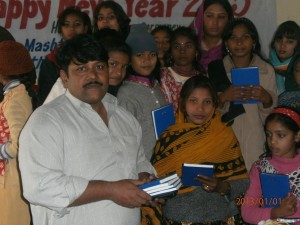 Children receiving books from Principal Amin Issac