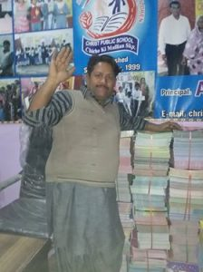 Principal Amin standing beside stacks of books